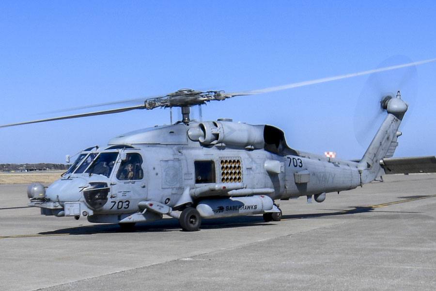 """210421-N-EJ241-2061    MISAWA, Japan (April 21, 2021) – Aviation Boatswain's Mate (Handling) 3rd Class Grant Daniels, assigned to Naval Air Facility (NAF) Misawa, salutes the crew of an MH-60R Sea Hawk, assigned to the """"Saberhawks"""" of Helicopter Maritime Strike Squadron (HSM) 77, as they take off from NAF Misawa. NAF Misawa provides aviation and ground logistic support and services to all permanent and transient U.S. Navy and U.S. Marine Corps forces in Northern Japan. (U.S. Navy photo by Mass Communication Specialist 2nd Class Jan David De Luna Mercado)"""